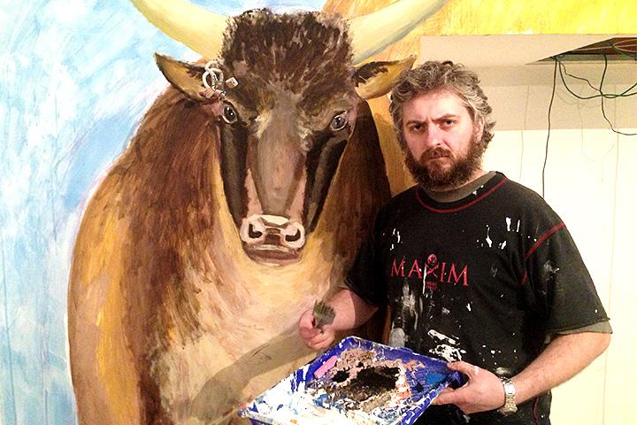 Художник Сергеев со своей росписью на стене будущего ресторана